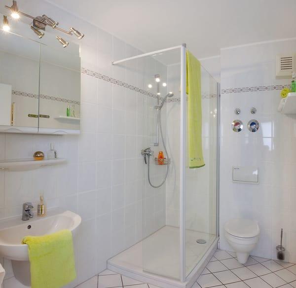 Das Badezimmer ist mit flacher Echtglasdusche, Waschtisch, WC, Handtuchtrockner und einem Haarfön ausgestattet.