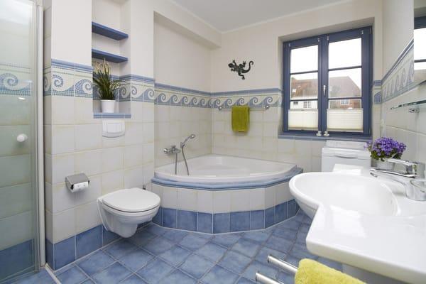 Das Badezimmer in maritimem Design verfügt über eine große Eckbadewanne.