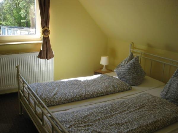 Schlafzimmer mit Doppelbett und begehbarem Kleiderschrank