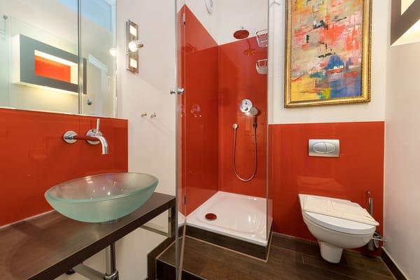 Das schicke Designbad bietet Ihnen Dusche, Waschbecken und WC.
