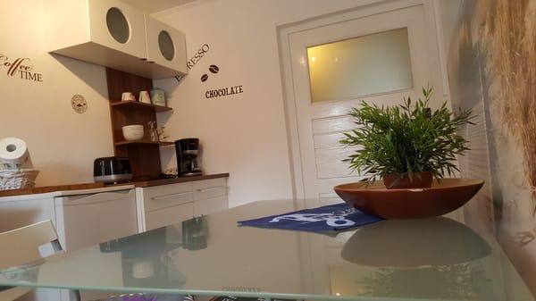 Küche ausgestattet mit Toaster, Kaffeemaschine, Eierkocher, Wasserkocher, Induktionsplatte und eine Mikrowelle mit intigriertem Grill und Heißluftofen.