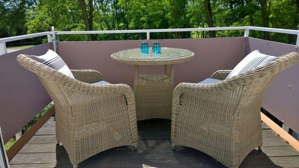 Balkon mit bequemen Sesseln und Esstisch