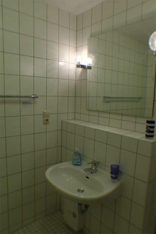 Das ca. 4m² große, weiß geflieste Bad ist mit Dusche und WC ausgestattet. Viel Ablagefläche und ein Föhn sind vorhanden.
