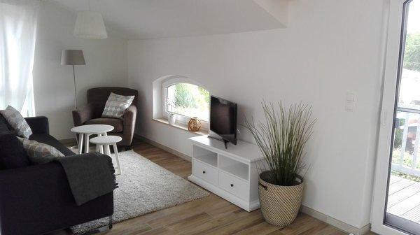 Gemütliches helles Wohnzimmer mit Balkon
