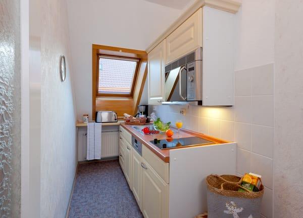 Links befindet sich ein Flur mit kleiner Pantryküche (kleine Ausstattung an Geschirr, Gläsern, Kühlschrank, Wasserkocher, Toaster, Kaffeemaschine, Kombigerät(2-Platten-Kochfeld mit Backfunktion).