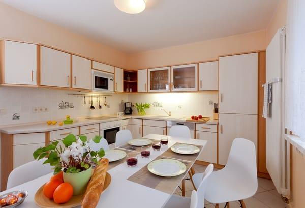 Eine separate Küche mit allen Extras (Spülmaschine, Kühlschrank, Gefrierschrank, Backofen, Mikrowelle, Ceranfeld, Toaster, Wasserkocher, Kaffeemaschine) und einem Esstisch, der Platz für die ...