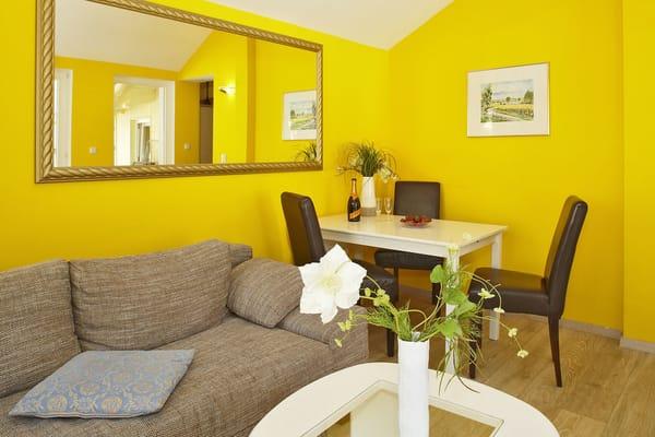 Der gemütliche und helle Wohnbereich mit bequemer Couch und Flat-TV, bodentiefen Fenstern und Essplatz lädt zu geselligen und unterhaltsamen Stunden ein.