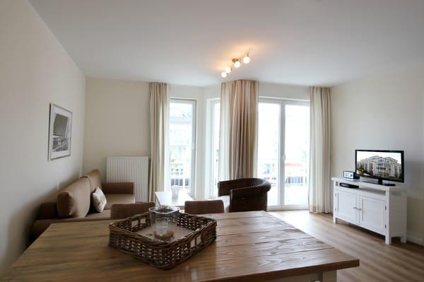 Wohnbereich mit Flachbild-TV sowie Zugang zum Balkon
