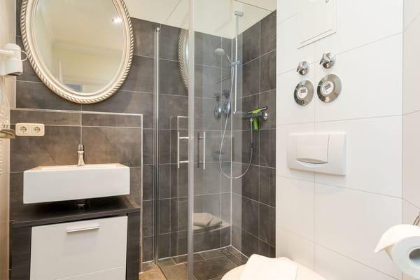 Das schicke neue Bad hat Echtglasdusche, WC und Fön.