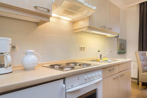Die Küchenzeile ist ausgestattet mit 4-Plattenherd, Backofen, Kühlschrank mit Gefrierfach, Kaffeemaschine, Wasserkocher, Toaster, Geschirr etc.