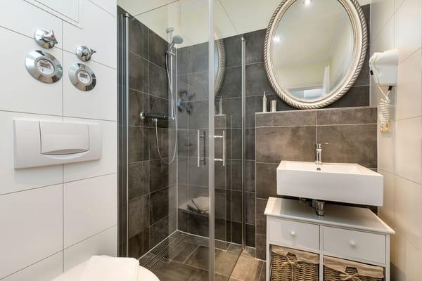 Das schicke Bad bietet Ihnen Fön, Echtglasdusche und WC.