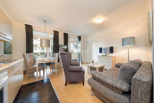 Das Wohnzimmer mit TV, Stereoanlage und kostenfreiem WLAN hat einen Austritt zum großen, möblierten Balkon.