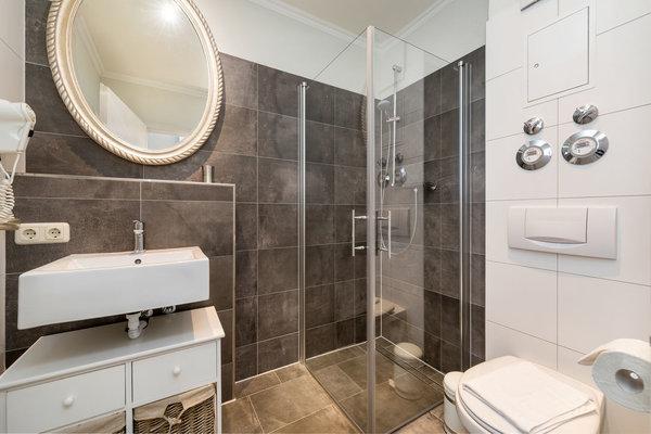 Das moderne Bad hat Echtglasdusche, WC und Fön.