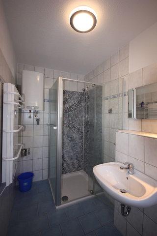 Bad mit tiefer Mosaikdusche und Handtuchwärmer