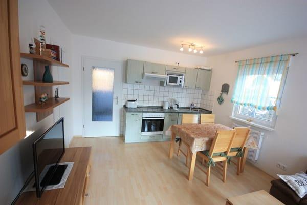 Esstisch und Küchenzeile mit Ofen und Mikrowelle