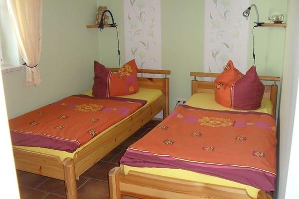 Schlafraum mit zwei Einzelbetten und großem Kleiderschrank