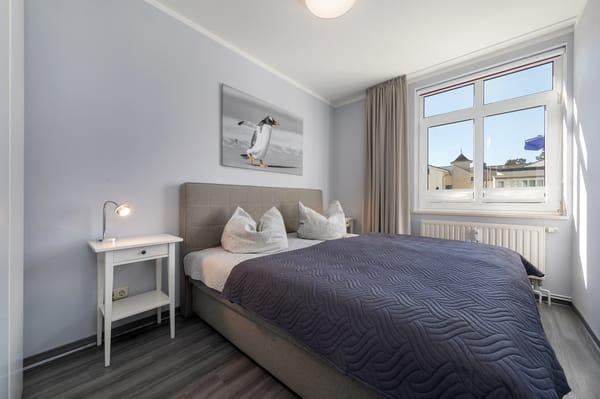 Das Schlafzimmerfenster hat Sichtschutzplissees und ein Innenrollo für die Verdunkelung.