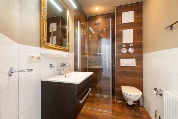Das schicke Bad hat eine bodengleiche Echtglasdusche, Fön und WC.