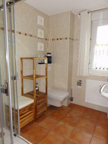 Im großen raumhoch gefliesten Bad befinden sich das WC, Dusche und der Waschtisch. Ein Fön befindet sich im Badschrank.