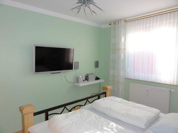 Ein Schlafzimmer ist mit einem TV und einer Stereoanlage mit CD und IPod Dockinstation ausgestattet. Der Boden ist mit Laminat ausgelegt.