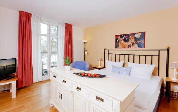 Der Wohnraum mit Flat-TV ist in warmen Farben gehalten und mit einem bequemen Doppelbett (180x200cm) ausgestattet.