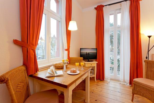 Der Wohnraum ist in warmen Farben gehalten, die gemütliche Polstersitzecke mit Flat- TV lädt zum Erholen und Ausspannen ein.