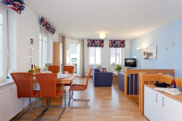 ... sowie einen Esstisch mit Schwingstühlen. Vom Wohnbereich gelangen Sie auf Ihren Balkon mit Zugang zum Garten.