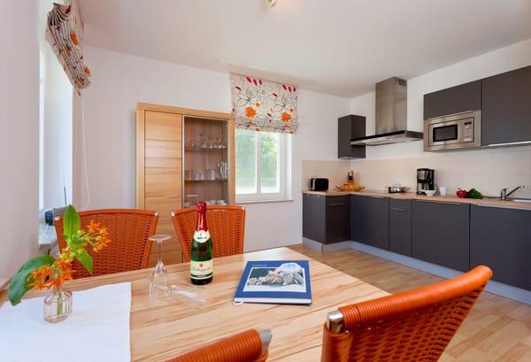 Die im Wohnbereich integrierte komplett ausgestattete Einbauküche verfügt zudem über Kühlschrank, Mikrowelle, ...