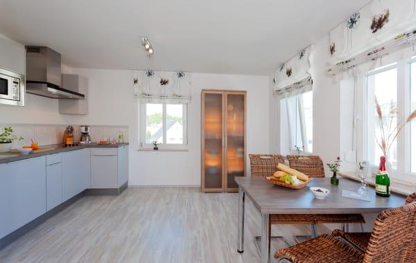 Die im Wohnbereich integrierte komplett ausgestattete Einbauküche verfügt zudem über Kühlschrank, ...