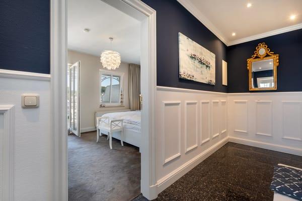 Blick vom Flur mit Garderobe in das Schlafzimmer.
