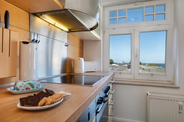 Geschirr, Besteck und Küchengeräte sind überwiegend von namhaften Marken. Auch im Küchenfenster sehen Sie das Meer.