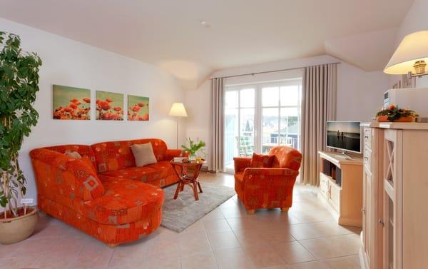 Ein bequemes Sofa, ein Sessel, Flat-TV sowie ein Esstisch für vier Personen laden zum Entspannen und geselligem Beisammensein ein.