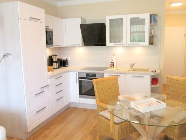Wohnküche - alles neu seit 2018: Küche inkl. Kühlschrank, Mikrowelle, Ceran-Kochfeld, Backofen, Geschirrspüler sowie Esstisch und Rattan-Stühle.