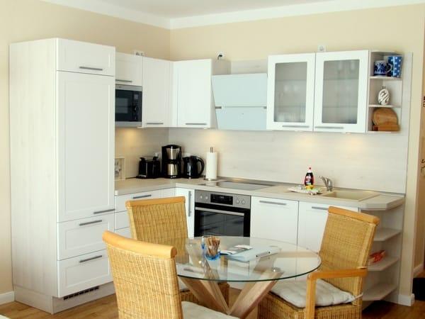 Wohnküche mit Kühlschrank, Mikrowelle, Ceran-Kochfeld, Backofen, Geschirrspüler sowie Esstisch und Rattan-Stühle.