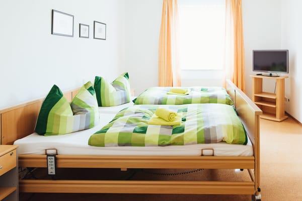 1. Schlafzimmer mit 2 elektr. Pflegebetten und 2. TV, Zugang zum Bad