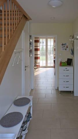 Eingangsflur mit Blick ins Wohnzimmer, Flyerregale beidseits