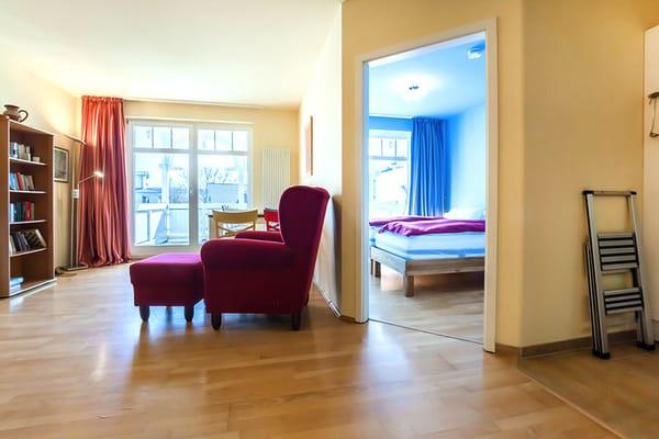 Wohnraum mit offener Tür zum Schlafzimmer