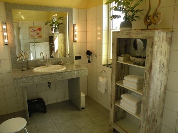Giebelhohes Bad mit zwei Fenstern, Granitwaschtisch, viel Ablagefläche, Fön, Glasdusche mit bequemen Eckeinstieg. Kosmetiktücher, WC-Papier, Seife inkl.