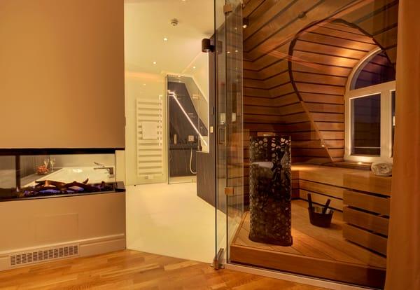 Komplettiert wird das Badezimmer mit einem Doppelwaschtisch, einer ebenerdigen Dusche sowie einem abgetrennten WC.