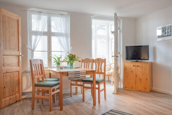 Wohnzimmer mit Esstisch und Flachbildfernseher