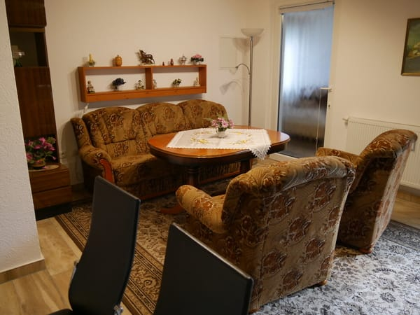 Wohnraum mit bequemer Sitzgruppe und Glastür zum Schlafraum