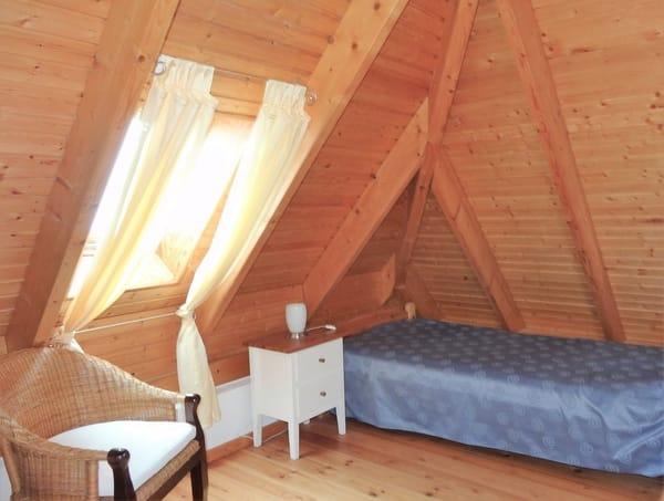 Schlafempore mit Einzelbett, der Bereich kann optisch mit einem Vorhang abgetrennt werden