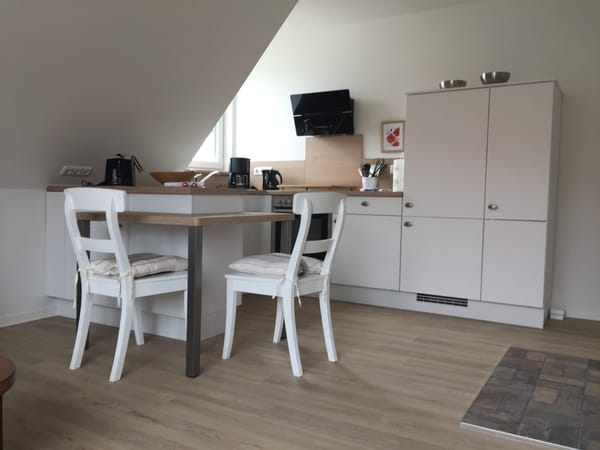 Küche mit Geschirrspüler, Cerankochfeld, Backofen, Kühlschrank mit Tiefkühlfach und Essplatz