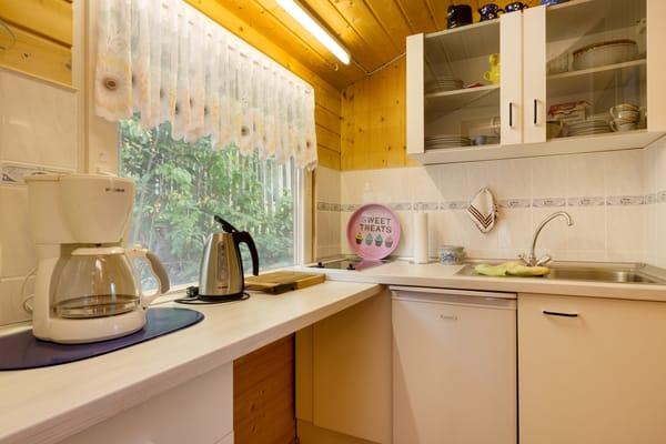 Die kleine Küchenzeile mit Kühlschrank, 2-Platten-Kochfeld, Kaffeemaschine, Wasserkocher und Toaster.