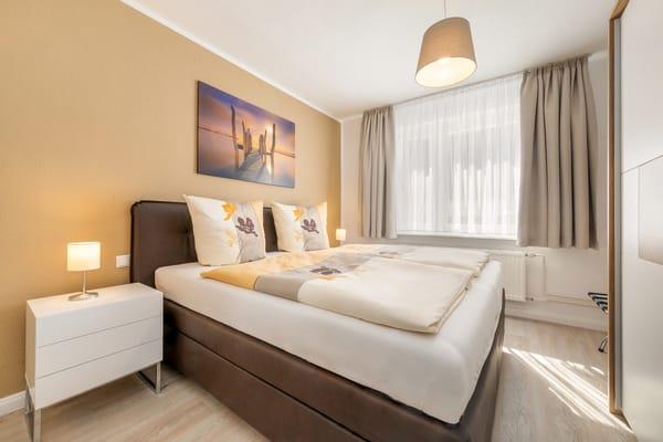 Schlafzimmer 1 hat Doppelbett (180x200cm), TV und einen großen Kleiderschrank.