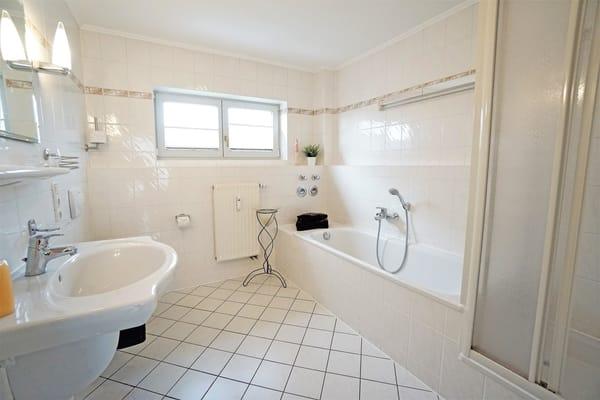 Badezimmer mit Badewanne und Duschkabine