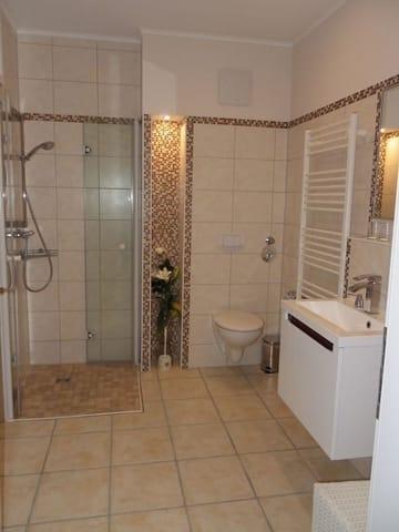 Bad mit Fön, Waage, Schrank, Duschhocker und 2. großem Spiegel. Hintere Badansicht