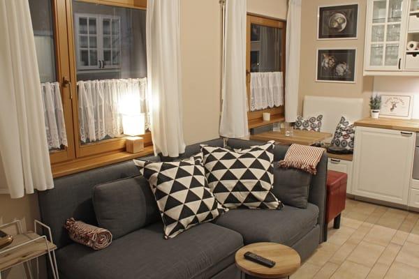 Gemütliche Couch mit Schlafmöglichkeit  und Küchensitzecke im Hintergrund