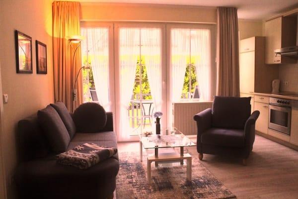 Wohnraum mit integrierter Küchenzeile und Essecke. Die Couch lässt sich zu einer Schlafcouch umfunktionieren.