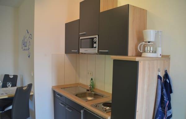Küchenzeile mit Mikrowelle, Kaffeemaschine, Wasserkocher, Toaster.